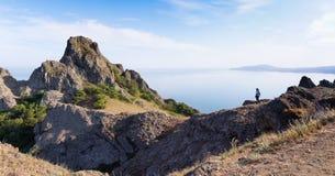 Tourist standing on a mountain. Stock Photos