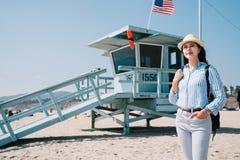 Tourist standing next to lifeguard station. A confident female tourist standing next to America`s lifeguard station stock images