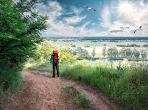 Tourist standing on the road atop hill under blue sky. A tourist with a backpack is standing on country road passing through hill above the river. Summer Stock Photos