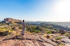 Tourist standing on rock and looking at expansive view of Jodhpur fort from above, perched on top dominating the blue town. Travel Royalty Free Stock Images