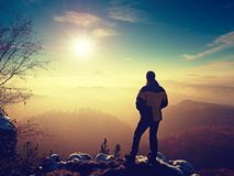 Tourist standing on rocky view point and watching into misty valley. Royalty Free Stock Image