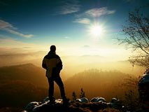Tourist standing on rocky view point and watching into misty valley. Stock Photos