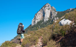 Tourist stands on hill and looks mountain Royalty Free Stock Images