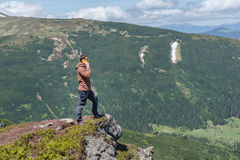 Tourist stands on the mountan cliffs speaking on the smartphone Stock Image