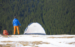 A tourist stands near a tent and a backpack. Royalty Free Stock Images