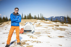 A tourist stands near a tent and a backpack. Stock Photo