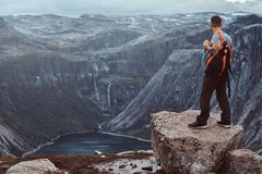 Tourist stands on the peak of the mountain with an amazing view of the Norwegian fjord. Tourist stands on the peak of the mountain with a beautiful view of the royalty free stock images