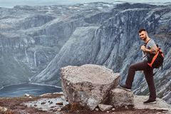 Tourist stands on the peak of the mountain with an amazing view of the Norwegian fjord. Tourist stands on the peak of the mountain with a beautiful view of the royalty free stock photos