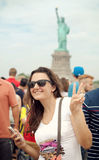 Tourist at Statue of Liberty making expression victory hand sign Royalty Free Stock Image