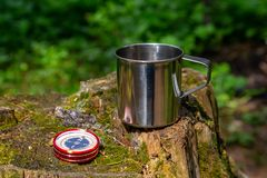 Tourist steel cup and compass in the summer forest.  stock images