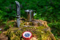 Tourist steel cup and knife in the summer forest.  stock image