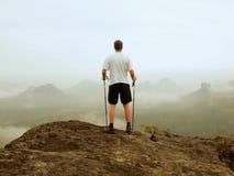 Tourist steht auf der Spitze des Sandsteinfelsens im felsigen Park und passt über das nebelhafte Tal des Morgens zu großem Sun au Lizenzfreie Stockfotografie