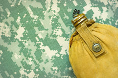 Tourist stock. Yellow tourist flask on a ACU camouflage background Stock Image