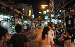 Tourist Street in Bangkok. BANGKOK, THAILAND - JUN 30, 2013: Nighttime view of people walking along a road in the Khao San area. The road is famous as Royalty Free Stock Image