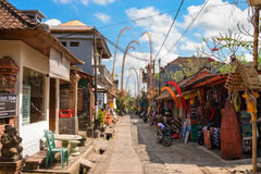 Tourist street decorated by traditional penjor on Bali. BALI, INDONESIA - SEP 19: Tourist street decorated by traditional penjor with shops and tours on Sep 19 Royalty Free Stock Photography