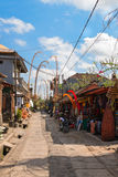 Tourist street decorated by traditional penjor on Bali Stock Photo
