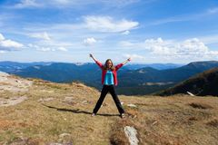 Tourist stretching out her arms while on mountain Royalty Free Stock Photography