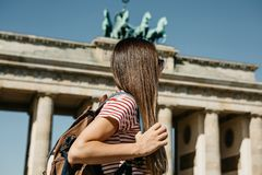 A tourist or a student with a backpack near the Brandenburg Gate in Berlin in Germany. A tourist or a student with a backpack near the Brandenburg Gate in royalty free stock images