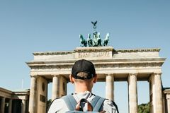 A tourist or a student with a backpack near the Brandenburg Gate in Berlin in Germany. A tourist or a student with a backpack near the Brandenburg Gate in stock photos