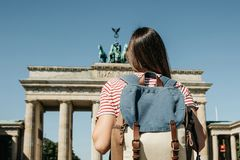 A tourist or a student with a backpack near the Brandenburg Gate in Berlin in Germany. A tourist or a student with a backpack near the Brandenburg Gate in royalty free stock image