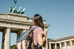 A tourist or a student with a backpack near the Brandenburg Gate in Berlin in Germany. A tourist or a student with a backpack near the Brandenburg Gate in royalty free stock photography