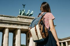 A tourist or a student with a backpack near the Brandenburg Gate in Berlin in Germany. A tourist or a student with a backpack near the Brandenburg Gate in royalty free stock photo