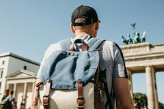 A tourist or a student with a backpack near the Brandenburg Gate in Berlin in Germany. A tourist or a student with a backpack near the Brandenburg Gate in stock photo