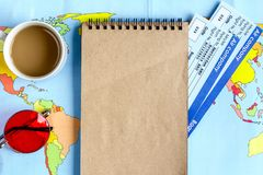 Tourist stuff with notebook and tickets on map background top vi. Tourist stuff with notebook, coffee and flight tickets on map background top view mockup Royalty Free Stock Photo