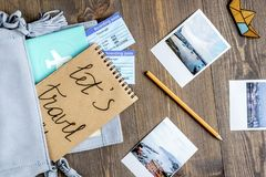 Tourist stuff with photos and tickets on wooden background top v. Tourist stuff with passport, photos and flight tickets on wooden table background top view Royalty Free Stock Photos