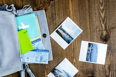Tourist stuff with photos and tickets on wooden background top v. Tourist stuff with passport, photos and flight tickets on wooden table background top view Royalty Free Stock Photography