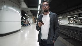 Guy waiting for train in Barcelona metro. Tourist in stylish clothes holding smartphone in hands, listening to music in Barcelona subway, moving by train on stock video footage