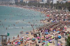 Tourist sunbathe or bath on the sea in crowded El Arenal beach in Mallorca Stock Images