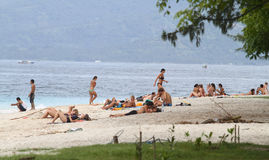 Tourist sunbathe at the beach Royalty Free Stock Images
