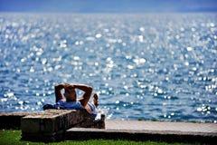 Tourist sunbathing on Ohrid Lake shore in summer Royalty Free Stock Images
