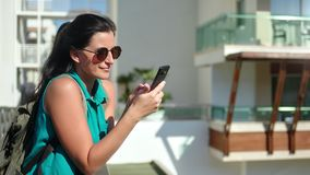Tourist sunny girl backpack smiling chatting using smartphone on terrace enjoying vacation stock video