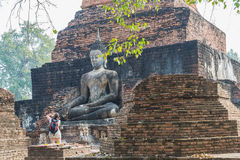 Tourist take photo of old buddha statue in the ancient temple Sukothai Thailand Stock Photo