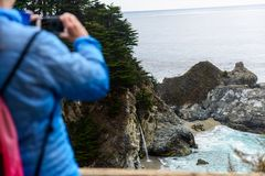 A tourist take a picture of the McWay Falls cove royalty free stock photos
