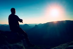 Tourist take a rest. Handsome young man sitting on the rock and enjoying view into misty rocky mountains. Royalty Free Stock Photos