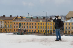 Tourist takes photo at the central square of the city in Helsinki, Finland. Royalty Free Stock Photography