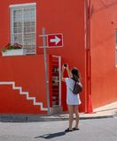 Tourist takes photo of colourful house in the Malay Quarter, Bo Kaap, Cape Town, South Africa. Historical area of painted houses. stock photo