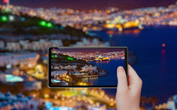 Tourist takes photo of night city Bodrum by tablet pc Royalty Free Stock Photo