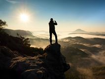 Tourist takes photos with smart phone on peak of hilly landscape. Autumn fogy hills Stock Photography