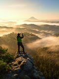 Tourist takes photos with smart phone on peak of hilly landscape. Autumn fogy hills royalty free stock photography