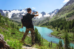 Tourist takes photos with smart phone on peak of hilly landscape. The beautiful landscape of the Altai Mountains. Multinskoe lake Royalty Free Stock Image