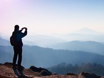 Tourist takes photos with smart phone on peak of rock. Dreamy fogy landscape, spring orange pink misty sunrise in a beautiful vall Royalty Free Stock Photo