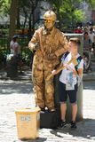 Tourist takes picture with firefighter human statue in Lower Manhattan. NEW YORK - JULY 16, 2017: Tourist takes picture with firefighter human statue in Lower royalty free stock images