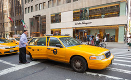 Tourist takes the yellow cab in Manhattan, NYC. NEW YORK CITY, NY, USA - JULY 07, 2015: Tourist takes the yellow cab in Manhattan near the store's Salvatore Stock Photography