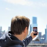Tourist taking mobile photo of skyscrapers Stock Photography