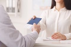Tourist taking passport with tickets at travel agency. Tourism concept. Tourist taking passport with tickets at travel agency royalty free stock photos