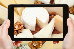 Tourist taking photo of assortment of cheeses Royalty Free Stock Photo
